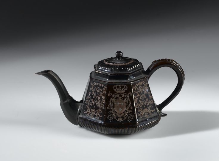 Octagonal teapot of red stoneware, polished and engraved on opposite sides with an escutcheon charged with a double L cypher and fleurs-de-lys: German, Saxony, Meissen, by Bottger, c. 1710
