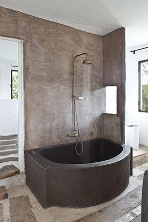 Mediterranean Rustic Bathroom: A custom concrete tub and brass shower fittings outfit a spare bathroom..