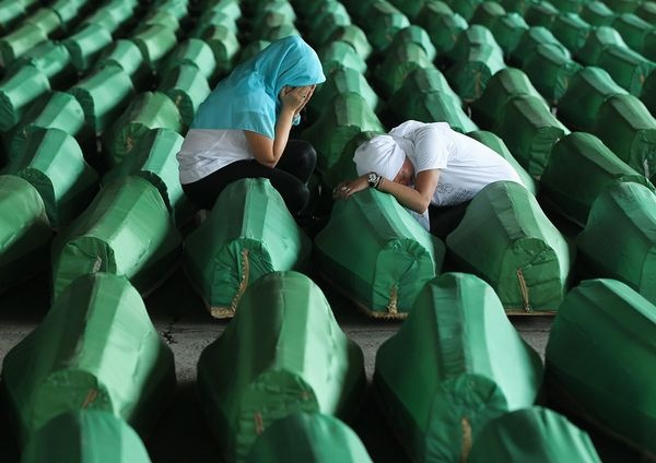 Two young Muslim women weep over a coffin, 1 of 613 containing victims of the 1995 Srebrenica massacre on July 10, 2011, in Potocari, Bosnia and Herzegovina