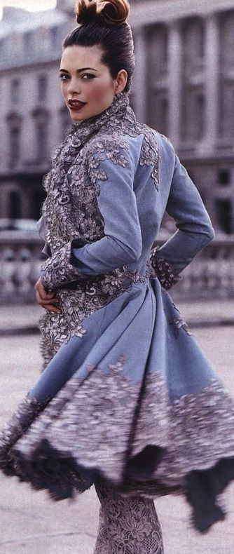 Actress Amelia Heinle at the Place de la Concorde in a Givenchi frock coat of turquoise silk moiré faille with antiqued silver lace appliqué, over pale gray lace trousers trimmed in crystal beads; an a silk taffeta blouse. Givenchy Haut Coutture 1999