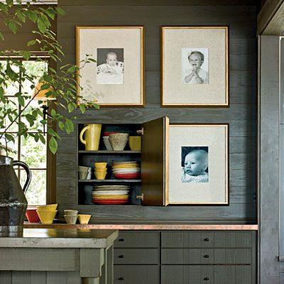 Disguised Cabinets | Framed family photos that act as cabinet doors disguise ample storage for dinnerware.