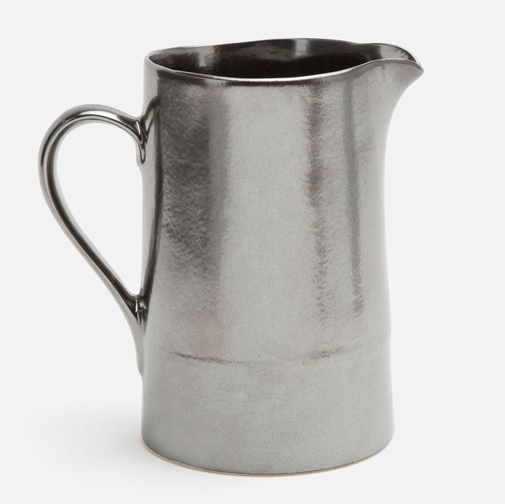 Simplicity is the hallmark of this stoneware pitcher, the metallic look adds a dramatic flourish to a classic piece. Its shape makes Ariana a welcoming addition to any table setting, no matter how minimal or eclectic.   Finish: Pewter  Material: Stoneware Dishwasher Safe Imported