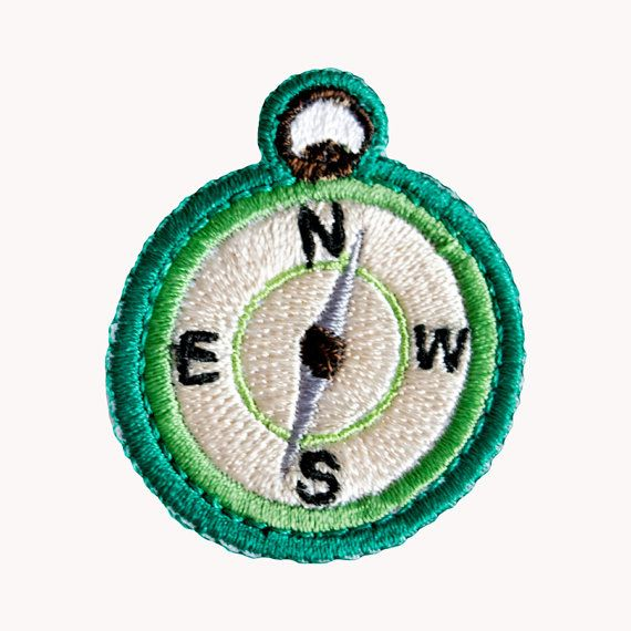 """This embroidered compass patch has a N S E W embroidered face with green and ocean blue stitching! Measures 1 3/4"""" wide and 2"""" long."""