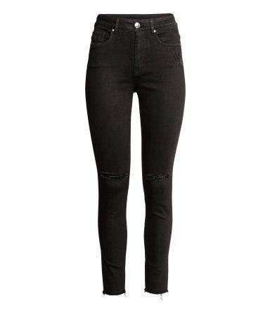 Svart. Ett par ankellånga 5-ficksjeans i stretchig denim med hårt slitna detaljer. Byxorna har supersmala ben och hög midja.