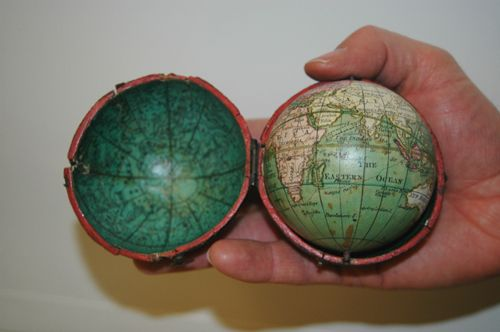 """1809 terrestrial """"pocket"""" globe.  2.75"""" diameter. Label pasted on: DOLLOND / LONDON / 1809. The globe consists of paper gores over wood, with a metal pivot at both poles. The paper gores are copper-engraved, hand-colored, and varnished. There is an accompanying folding case of wood covered in embossed paper, the interior lining of the case shows an inverted celestial globe."""