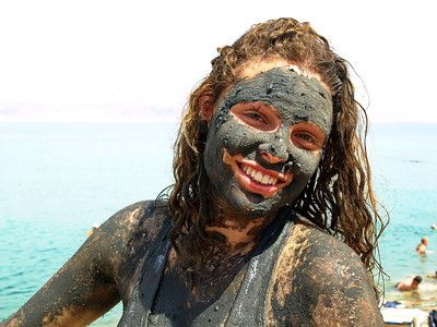 Girl covered in Dead Sea mud