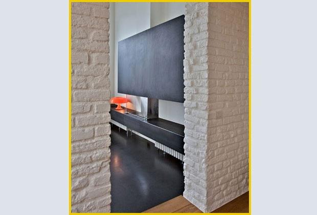 Muro in mattoni grezzi dipinto di bianco, pavimento in cemento colorato in massa e tavolato.