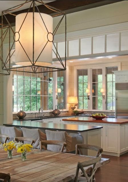 This amazing kitchen has lots of glass features we love - translucent transom windows above the opening to the dining area, plus big windows with matching French doors, both with grids that really add to their beauty. We install windows and doors in the Minneapolis MN area. http://www.replacementwindows.com