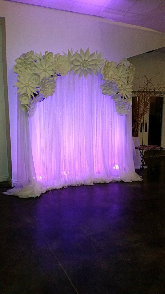 Moments In Time Wedding  & Event Rentals ~ 8' H x 7' W Pipe & Drape, dressed with white sheers, crystal curtains, paper flowers, uplights.   Image taken at Chancey's Event Center.  Please reach us at 406.208.9549. Uses: head table, cake table, photo booth backdrop.