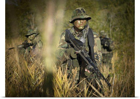 U.S. Navy SEALs walk through tall grass during combat operations