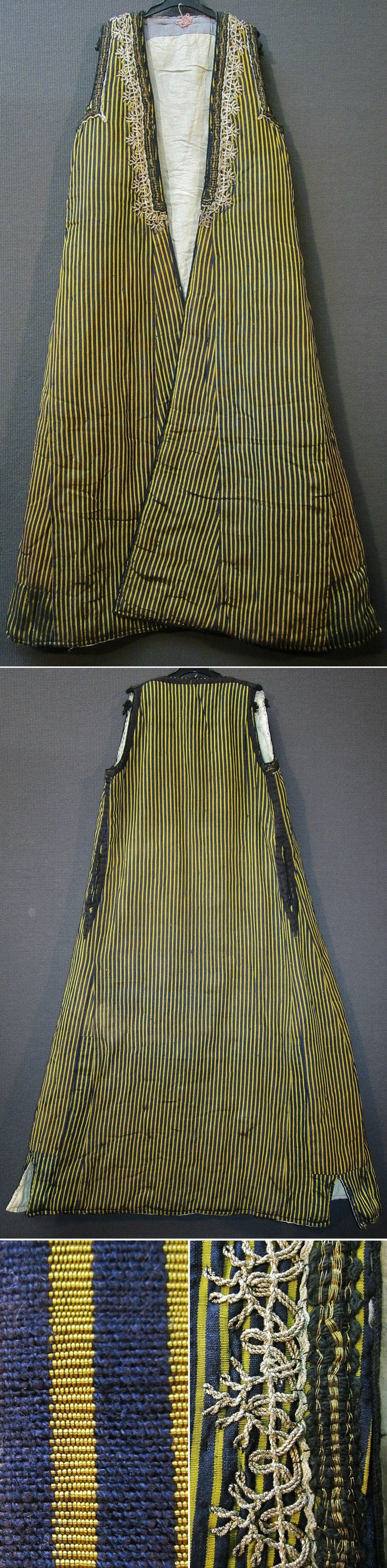 Traditional sleeveless caftan for women, from the rural Bartin region, ca. 1925-1950.  Sometimes called 'uzun yelek' (long vest) or (locally) 'uskuta'.  Made of a striped silk fabric; quilted and lined with white cotton.  The neck is adorned with metallic (silver) thread embroidery and black & golden braid; the armholes additionally feature some (small) black silk tassels.   (Inv.n° kaf013 - Kavak Costume Collection - Antwerpen/Belgium).