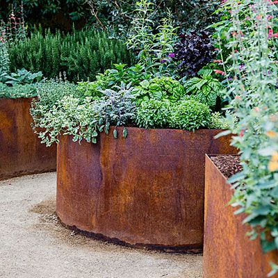 Corten steel garden containers lushly planted with herbs.