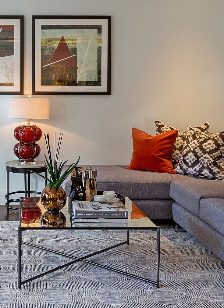 This Andrew Martin Agnes blown-glass lamp with mid-century curves and contemporary polished iron fittings sits atop the elegant Andrew Martin Hawk side table, adding a warm pop of rouge to our living room design.