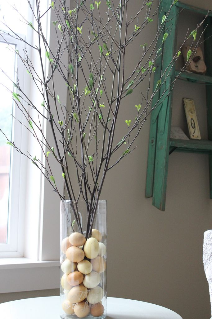 Really simple spring table decorating idea: put inexpensive plastic craft eggs in a hurricane and fill with spring sticks!