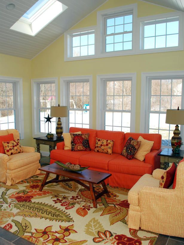 Rich, vibrant hues and dark wood furnishings emit visual warmth in this country-style living room. Pale yellow walls tone down the bold sofa and reflect the softer shades visible in the area rug's floral design. Rustic decorative stars pull in the country feel in a simple and subtle way. Design by Helen Richardson