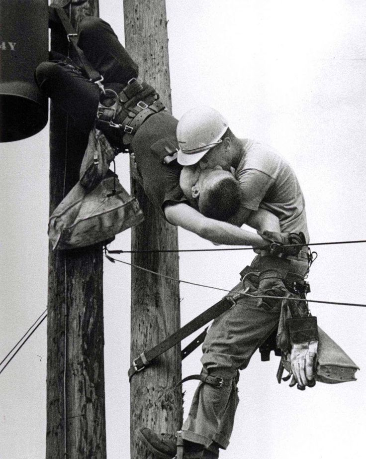 """""""The Kiss of Life"""" July 17 1967 Jacksonville FL. Electrical lineman J.D. Thompson ran about 400 feet and climbed a 20-foot pole to help his friend Randall Champion who had touched a hot wire. Newspaper photographer Rocco Morabito was driving by and took this Pulitzer Prize-winning photo."""