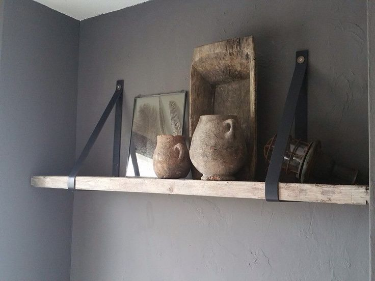 Oude houten plank met leerbanden aan de muur bevestigd.