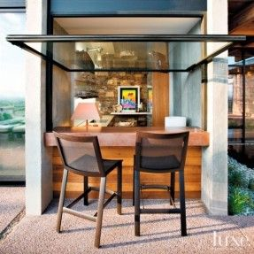 on this patio a pair of woven mesh and aluminum barstools belly up to the outside counter where a window that opens to a wet bar in the living