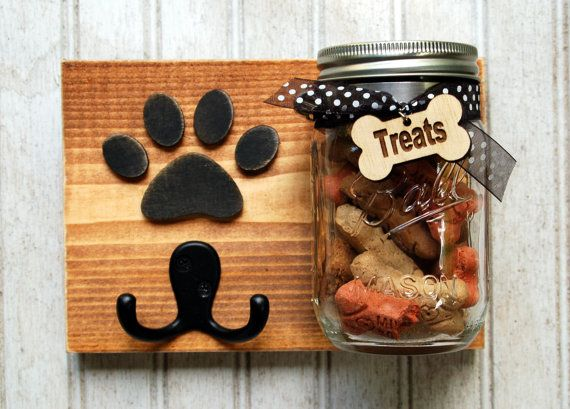 Dog leash holder and treat jar. Cute and practical, this treat/leash holder combination measures 8 x 6 long. All the wood is recycled or culled to create a functional piece of art. On the back are two heavy duty key hooks to assure proper hanging with bumpers to protect your wall. Each piece is hand cut and painted. The mason jar is attached with a hose clamp, and if need be can be loosened for cleaning. This piece is sold as is, but custom orders are available, which can include, single or…