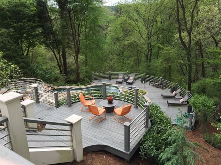 Multiple level deck with metal railings and view of trees from hillside