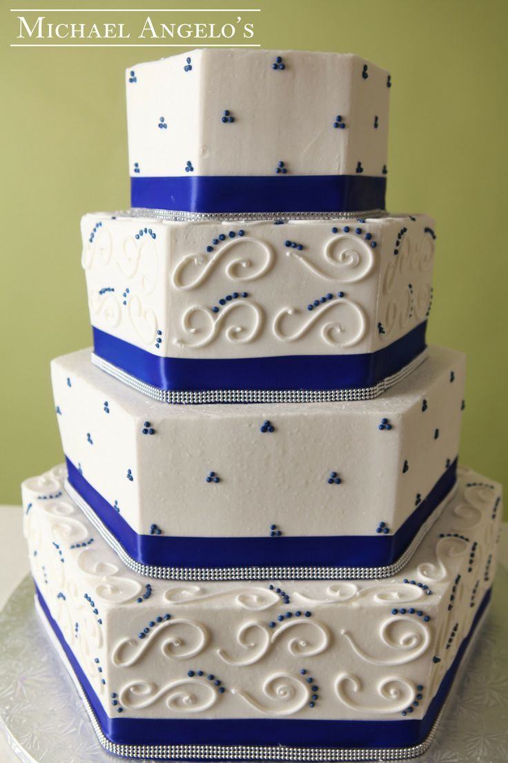 Royal Blue Bliss #10Gems  This four-tier buttercream hexagon cake is wrapped with a royal blue satin ribbon that is accented with gem ribbon, swirls and polka dots.