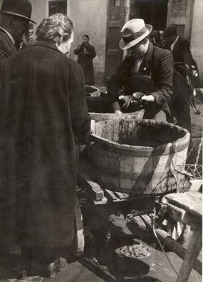 Utcai halárus kínálja portékáját kordéra rakott dézsákból, 1930-as évek.