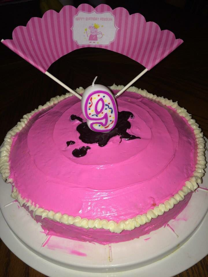 """Peppa Pig cake. After I bumped the icing with the cake topper. Pink swirly icing, """"like a pig's tail,"""" muddy puddle jumping candle."""