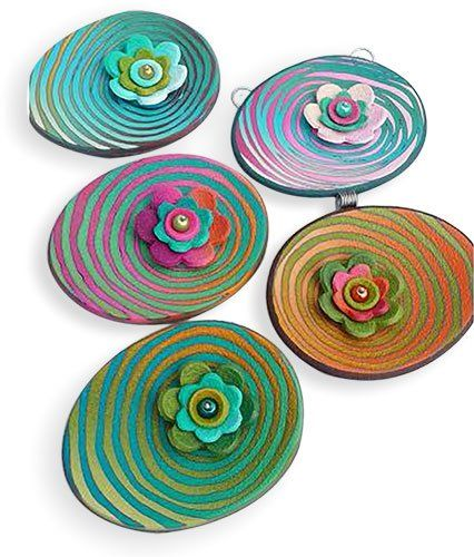 Simple layered polymer flower cutouts float on ovals of rippling colors in the same pallete. You may find yourself pondering how Eva Haskova created the graceful spirals on top of the graduated colors. You can learn her methods if you can get t [...]