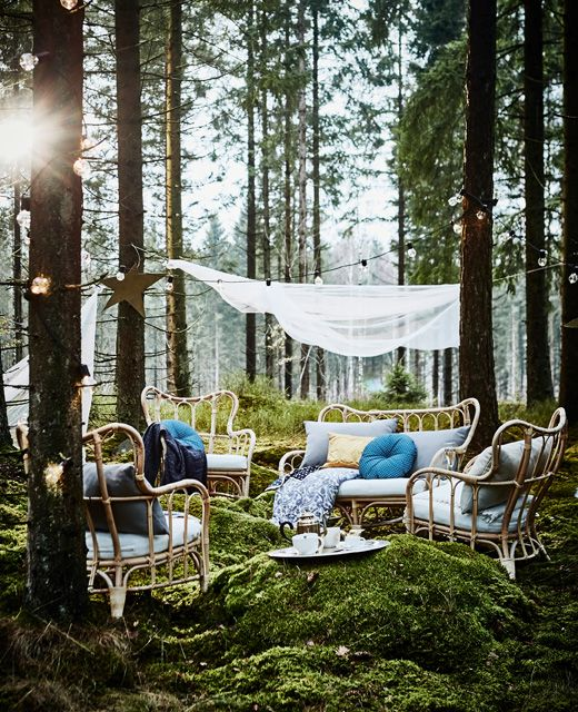 A lounge area in a forest wedding with rattan armchairs, lots of cushions and lighting chains