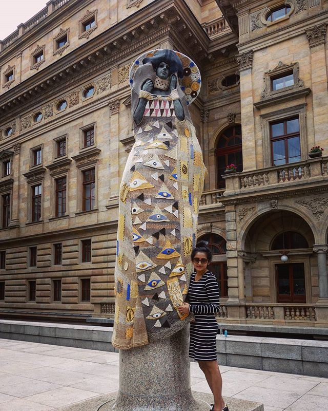 """Crocheted Klimt!  Czech costume designer Eva Bláhová draws inspiration from Klimt's #TheLadyInGold and I think she picked just the right sculpture to drape, not because it prominently sits at the entrace to the #NationalTheatre and beckons art lovers but because the crochet hangs over an interesting   socialist modernist sculpture titled """"Rebirth"""" by Josef Malejovsky.   #VaclavHavelSquare #Prague #GustavKlimt #josefmalejovsky   I just wanted to get under it ☺"""