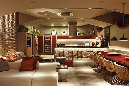 lounge bar com espaço gourmet e cozinha cadeiras design forro irregular exaustor de ilha e painel de rolhas
