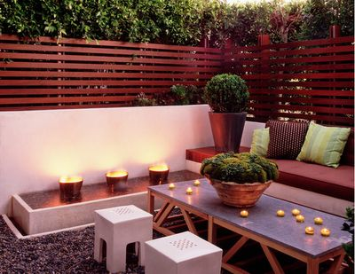 I like the wall and fence as well as the comfy seating in this pretty outdoor seating nook