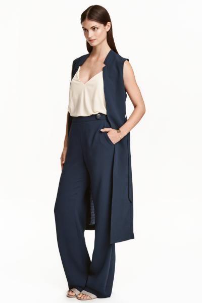 Široké kalhoty: Široké kalhoty ze strukturované tkaniny. Mají vysoký pas s poutky a knoflíky, skrytý boční zip, postranní kapsy a zadní výpustkové kapsy.