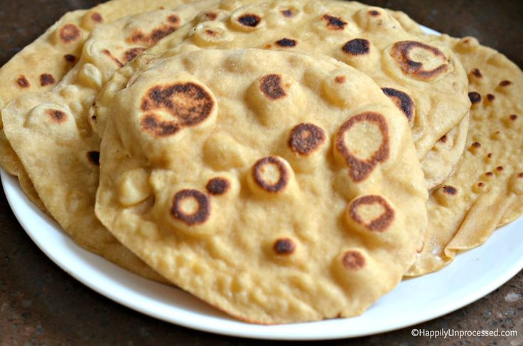 Homemade Naan Bread is so much easier to make than you think, and it's kind of fun too! Love brushing it with this garlic infused butter and watching the bread puff up! #Naan #bread #healthy www.happilyunprocessed.com