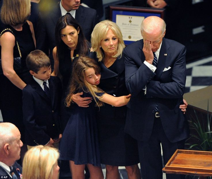 Vice President Joe Biden, right, rests his head in his hand during a viewing for his son Beau Biden on Thursday at Legislative Hall in Dover, Delaware. Standing with Biden (from left) are Beau Biden's widow Hallie with son Hunter; Beau's daughter Natalie embraces the VP's wife Dr Jill Biden