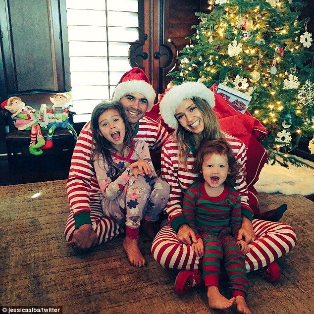 One happy family: The Dark Angel star shared this image with her husband Cash and two children on Christmas morning by the tree