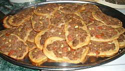 "Sfiha (Arabic: صفيحة‎ sfīḥah), also known as ""Arab Pizza"", is an Arab pizza-like dish originating from the Arabian Peninsula and Levant, and introduced in Brazil by Levantine immigrants, where it is known as esfiha. In contrast to the modern use of lamb or beef, traditional sfiha are open-faced meat pies made with ground mutton. Historically, sfiha were much like dolma—simply ground lamb, lightly spiced, wrapped in brined grape leaves."