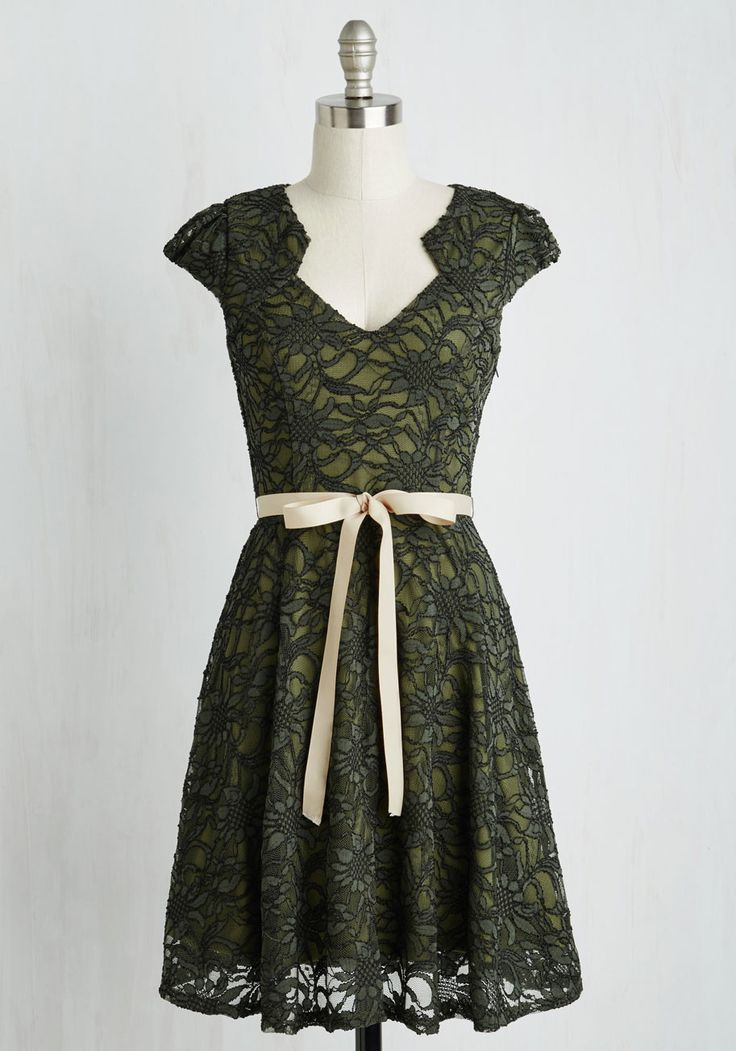 While standing in your closet full of precious pieces, you often find yourself reaching for this olive green! With its pale tan ribbon sash, unique notched neckline, and lace overlay filled with black embroidery, this fetching frock is the perfect foundation for your accessories.