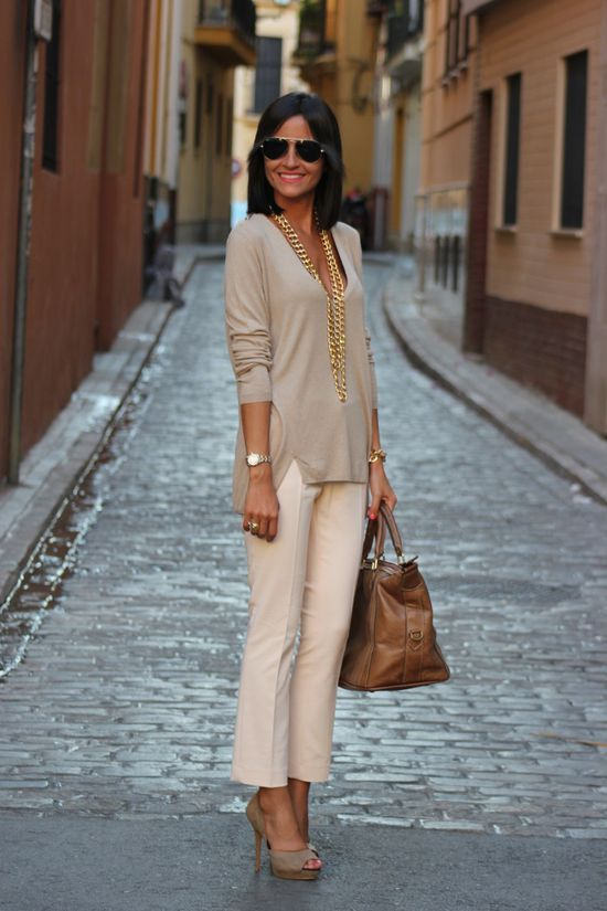 Smiling lobbed tanned brunette in blush slightly flared trousers, nude stilplats & matching V-neck untucked blouse, aviator shades bearing caramel handbag; salmon brick & brown stucco walls flanking narrow pavered street w/ mustard walls beyond