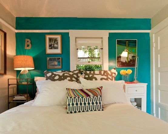 bed in front of a window.  no headboard.  the accent wall anchors it. along with the art and side tables.