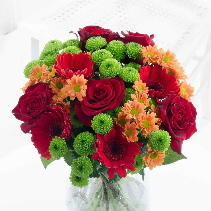Autumn Warmth: Deep red roses and gorgeous orange chrysanthemums pose beautifully to create our vibrant Autumn Warmth bouquet.