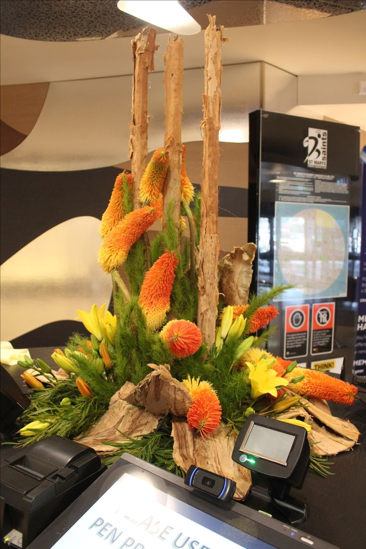 Fiery Large Corporate Arrangement with Orange and Yellow Pokers and Lily and Paperbark Poles and Leaves. created by Poppies and Peas Floral Design.