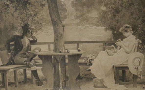 Fotografía enmarcada, muestra una escena en un jardín, con estatua de fondo y una pareja, hombre y mujer, sentados en dos bancos alrededor de una mesa. La mujer lleva un vestido largo y cose tranquilamente una prenda mientras es observada por el hombre con atuendo militar. Marco rectangular, de madera ebonizada, tipo casseta, con filo dorado. #Fotografías