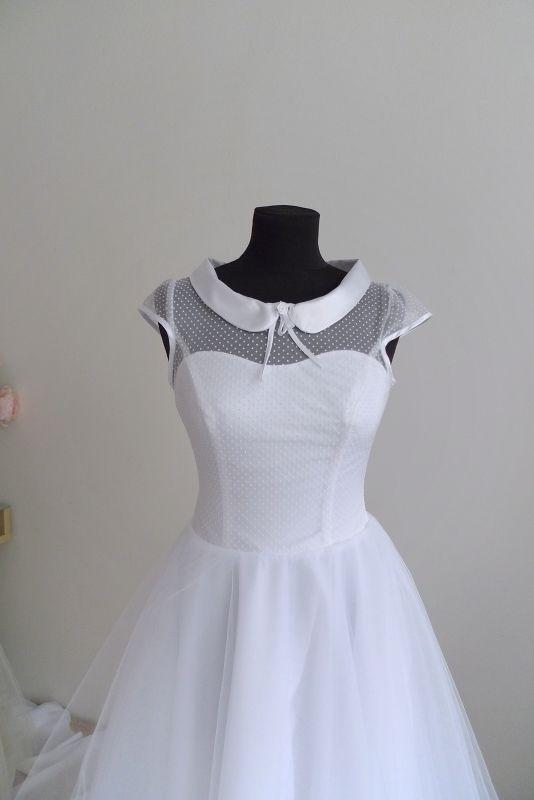 Puntíkaté svatební šaty Svatební šaty s polodlouhou kolovou sukní z mnoha vrstev jemného tylu, živůtek z puntíkaté látky, krátké rukávky. Výstřih a průramky lemované saténovou stužkou. Výstřih je množné zakončit položeným límečkem. Vzadu zip. Velikost podle přání, tyto byly na zakázku.