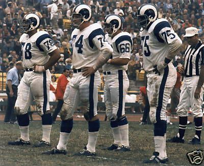 "Los Angeles Rams defense, featuring two of the Fearsome Foursome: Merlin Olsen (74) and David ""Deacon"" Jones (75)."