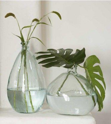 Mooie helder glazen vazen in ronde vormen, simpel met grote bladeren voor een natuurlijke stijl