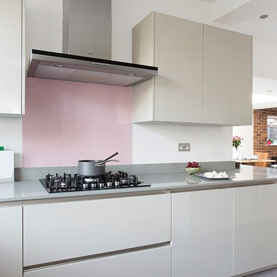 Contemporary kitchen with grey handleless cabinetry and pink splashback