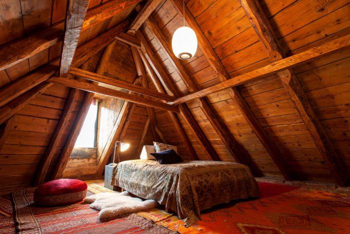 天井の低い屋根裏はベッドルームに最適! 海外でもベッドルームに利用する例が多いようです。このお部屋も木のぬくもりとウールのラグやベルベットのクッションの組み合わせが、あたたかな雰囲気を醸し出しています。