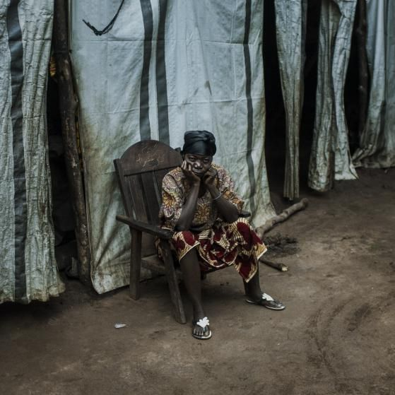 A displaced woman sits by her tent made by plastic sheeting in a camp for internally displaced people in Kaga Bandoro, Central African Republic, July 30, 2015.