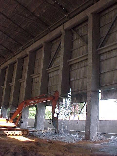 AMPUTAÇÃO DE PILARES: Foi possível amputar alguns pilares de galpão industrial para acréscimo de vãos entre os pilares remanescentes. O trabalho consistiu em reforçar a estrutura de concreto armado, criar uma estrutura auxiliar para transferência de cargas aos pilares remanescentes, cortar a seção dos pilares na cota desejada e finalmente amputar as partes dos pilares entre a fundação e as seções reforçadas. - Tecknicas Especiais de Engenharia Ltda - www.tecknicas.com.br
